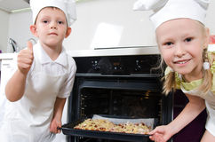 Happy excited young children with homemade pizza. Happy excited young children dressed white chefs uniforms grinning camera they place baking tray homemade pizza Royalty Free Stock Images