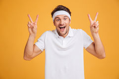 Happy excited young male athlete shouting and showing victory sign. With both hands over yellow background Royalty Free Stock Images