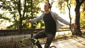 Happy excited young man riding bike in the park and listens to the music in black headphones. Man with outstretched