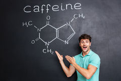 Happy excited young scientist showing chemical structure of caffeine molecule Stock Photography