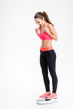 Happy excited young sportswoman standing on weigh scale Stock Photos