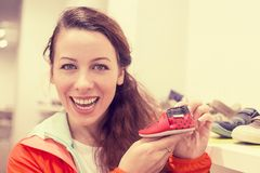 Happy excited young woman buying shoes for her child Royalty Free Stock Photo