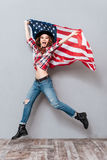 Happy excited young woman holding USA flag and jumping Stock Images