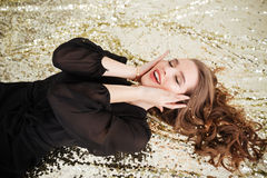 Happy excited young woman lying with eyes closed Royalty Free Stock Photo