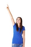 Excited young woman pointing on copy space Stock Photography