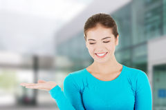 Happy , excited young woman presenting copy space Stock Images