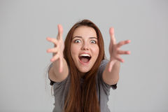 Happy excited young woman shouting and reaching hands to camera Stock Photos