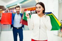 Happy excited young woman show credit card and holding  packages. Happy excited young women show credit card and holding  packages with her  laughing boyfriends Stock Photography
