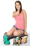 Happy Excited Young Woman Sitting on an Overflowing Suitcase Smiling Stock Images