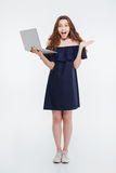 Happy excited young woman standing and holding laptop Stock Photography