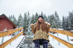 Happy excited young woman standing and shouting  in winter forest Stock Photo