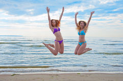 Happy excited young women in bikini jumping on beach Royalty Free Stock Photos