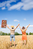 Happy exciting couple with valise rising hands Stock Image