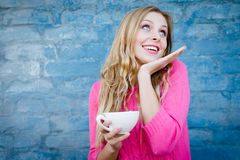 Happy exciting girl holding cup of beverage over brick wall. Royalty Free Stock Photos