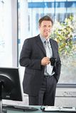 Happy executive at desk with coffee mug Stock Images
