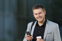 Happy executive holding a phone looking at camera Stock Photo