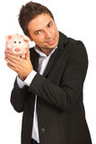 Happy executive listen to piggy bank Stock Photo