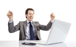 Happy executive man looking a laptop computer with arms raised i Stock Images