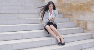 Happy executive with phone and seated on stairs stock video