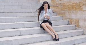 Happy executive with phone and seated on stairs Royalty Free Stock Photo