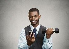 Happy executive reading good news on smart phone, lifting weight Royalty Free Stock Photography