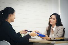 Happy executive or secretary giving documents to a businesswomen royalty free stock photography