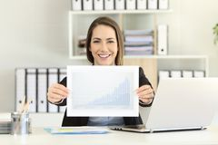 Happy executive showing a growth graph. Front view portrait of a happy executive showing a growth graph at office Stock Photos