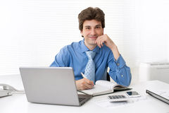 Happy executive sitting in front of laptop Royalty Free Stock Image