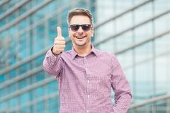 Happy executive in sunglasses showing thumbs up outdoors. royalty free stock photos