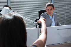 Happy executives celebrating success with fist bump. In the office stock images
