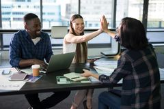 Happy executives giving high five to each other. In office Stock Photo