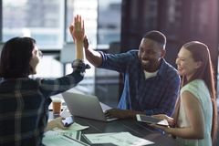 Happy executives giving high five to each other. In office royalty free stock photo