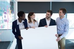 Happy executives holding a blank banner. In office stock photography