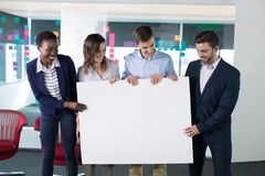 Happy executives holding a blank banner. In office royalty free stock photos