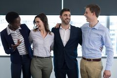 Happy executives interacting with each other. In office Royalty Free Stock Photos