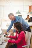 Happy executives interacting with each other while working at desk. In office Royalty Free Stock Photo