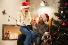 Happy exited beautiful woman in Santa`s hat getting gift box fro Stock Photography