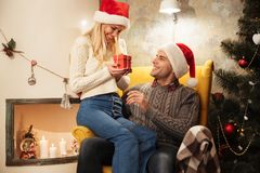 Happy exited blonde woman in Santa`s hat holding gift box while Stock Image