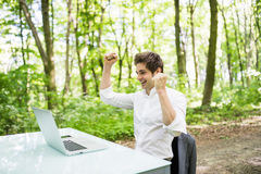 Happy exited freelancer with raised hands up celebrate success in job or great news in front of laptop at office desk in green par Royalty Free Stock Photography