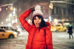 Happy exited woman having fun on city street of New York under the snow at winter time wearing hat and jacket. royalty free stock photography