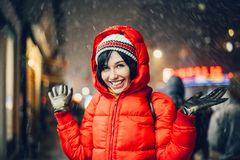 Happy exited woman having fun on city street of New York under the snow at winter time wearing hat and jacket royalty free stock images