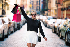 Happy exited woman walking with shopping bag on city street and enjoying shopping Stock Image