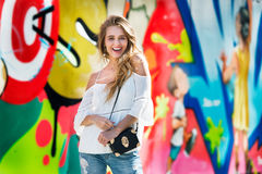 Happy exited young woman enjoying the life and standing outdoors near graffiti wall and looking at camera. Stock Photos