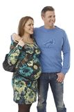 Happy expectant couple embracing. Happy young expectant couple embracing, looking away, smiling royalty free stock image