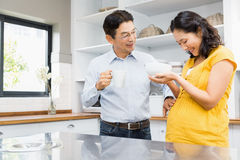 Happy expectant couple in the kitchen Royalty Free Stock Photos