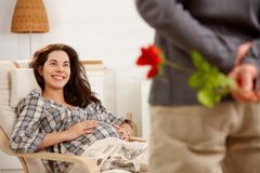 Happy expectant couple in nursery. Happy expectant couple wearing arabic style clothes, husband listening baby Royalty Free Stock Photos