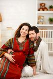 Happy expectant couple in nursery. Happy expectant couple wearing arabic style clothes, husband listening baby Royalty Free Stock Image