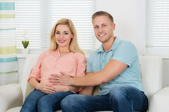 Happy Expectant Couple Sitting On Sofa At Home Royalty Free Stock Photography