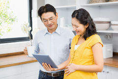 Happy expectant couple using tablet Royalty Free Stock Photos