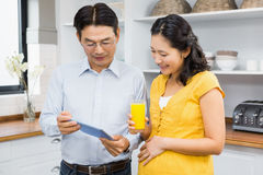 Happy expectant couple using tablet Stock Photos
